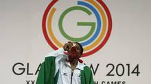 Chika Amalaha of Nigeria kisses her gold medal for winning the women's 53 kg weightlifting competition at the Commonwealth Games (Alastair Grant/AP)