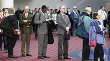 Job seekers stand in line at the Career Expo job fair in Portland, Ore. As a result of technology, more white-collar jobs are evaporating and making it difficult for the middle class to switch to another occupation. (Rick Bowmer/Rick Bowmer/AP)