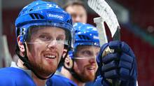 Daniel Sedin (left) of the Vancouver Canucks and teammate and twin brother Henrik Sedin look on from the bench during their first postseason practice at Rogers Arena in Vancouver, Canada April 9, 2012. (Jeff Vinnick/©2012 Jeff Vinnick/The Globe and Mail)