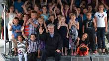 Prime Minister Stephen Harper poses for a photo on the tailgate of a Hercules aircraft with summer camp kids as he arrives in Hay River, NWT, on Aug. 19, 2013. (SEAN KILPATRICK/THE CANADIAN PRESS)
