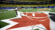 A worker paints a CFL logo in Montreal (Paul Chiasson/The Canadian Press)