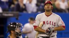 Los Angeles Angels Vernon Wells (right) walks towards the home plate as Toronto Blue Jays catcher J.P Arencibia looks on during the second inning of MLB baseball action in Toronto on Monday September 19, 2011. (Chris Young/THE CANADIAN PRESS)