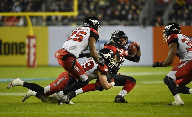 Kienan Lafrance of the Ottawa RedBlacks is tackled by the Calgary Stampeders' Tommie Campbell and Alex Singleton. Ottawa took the game 39-33 in a overtime thriller.