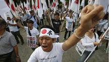 Protesters holding Japanese flags punch their fists during an anti-China rally in Tokyo Sept. 22. (TORU HANAI/REUTERS)