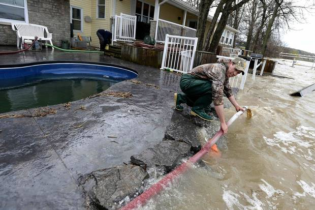 May 7: Martin Gervais works to get a pump's hose flowing again as water crashes against a rock wall at a home in Rockland, Ont., about 40 kilometres east of Ottawa.