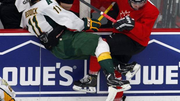 National Juniors selection camp player J.C. Lipon, right, from Regina, Sask., checks University of Alberta Golden Bears' Kruise Reddick during an exhibition game in Calgary, Alta., Wednesday, Dec. 12, 2012. (Jeff McIntosh/THE CANADIAN PRESS)
