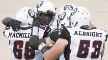 Ottawa Redblacks' Chevon Walker, second left, celebrates with teammates Nolan MacMillan (66) and Matthew Albright (53) after scoring against the Montreal Alouettes during first half CFL football action against the Montreal Aloutttes in Montreal, Friday, June 20, 2014. (The Canadian Press)