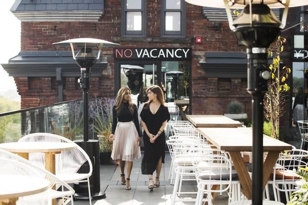 Natasha Deen, left, and Erika Hogerwaard walk on the rooftop patio of the Broadview Hotel in Toronto.