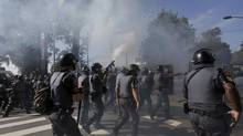 Riot policemen fire tear gas at demontrators during a protest against the 2014 World Cup in Sao Paulo (RICARDO MORAES/REUTERS)