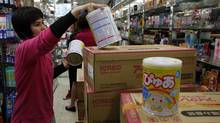 A staff member unpacks Japanese milk powder for a customer inside a store in Hong Kong March 16, 2011. Hundreds of people in the territory, worrying that future Japanese baby products will be contaminated by radiation, have lined up for milk powder. Radioactive materials spewed into the air by Japan's earthquake-crippled nuclear plant may contaminate food and water resources, with children and unborn babies most at risk of possibly developing cancer. (BOBBY YIP/Bobby Yip/Reuters)