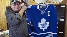 Chief Eli Moonias holds up an autographed Toronto Maple Leafs' Wendel Clark jersey, a Christmas present from the Noront mining company, on the Oji-Cree reserve Tuesday, Dec. 18, 2012 in Marten Falls, Ont. (Ryan Remiorz/The Canadian Press)
