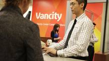 """Vancity teller Tim Lu helps a client at the company's head office in Vancouver in this file photo. Vancity has a new product, the 'Fair & Fast Loan."""" (Lyle Stafford For The Globe and Mail)"""