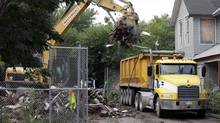Debris is loaded onto a truck at a house where three women were held captive and raped for more than a decade, Wednesday, Aug. 7, 2013, in Cleveland. Authorities want to make sure the rubble isn't sold online as 'murderabilia,' though no one died there. (Tony Dejak/AP)