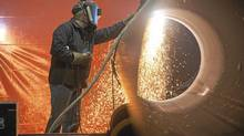 A welder uses a plasma torch to cut through pipe at the PCL Fabrication Facility in Nisku, Alta. (Ian Jackson For The Globe and Mail)