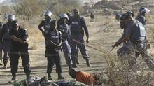 Policemen give instructions to an injured miner after the striking miners were shot outside a South African mine in Rustenburg, 100 kilometres northwest of Johannesburg, August 16, 2012. (SIPHIWE SIBEKO/REUTERS)