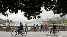 Tourists take photographs as cyclists pass by at Stanley Park in Vancouver, B.C. (DARRYL DYCK/THE CANADIAN PRESS)