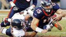 Denver Broncos quarterback Tim Tebow is tackled by Chicago Bears linebacker Brian Urlacher during their NFL football game in Denver December 11, 2011. The Broncos won 13-10 in overtime. REUTERS/Rick Wilking (Rick Wilking/Reuters)