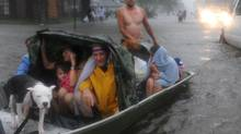 Residents of the Cambridge neighbourhood of LaPlace, La., flee rising flood waters associated with Isaac on Wednesday. The slowing hurricane was downgraded to a tropical storm, but its effects continued to wreak havoc. Isaac pushed water from lakes Pontchartrain and Maurepas into parts of LaPlace. (Arthur D. Lauck/Associated Press)
