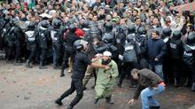 A riot policeman restrains a rock-wielding protester Friday as opponents of Egyptian President Mohammed Morsi clash with Islamist supporters of the President in Alexandria, Egypt. (AP)