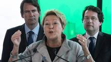 PQ leader Pauline Marois, flanked by candidates Pierre Karl Peladeau, left, and Bernard Drainville reponds to a question during a news conference Friday, March 21, 2014 in Longueuil, Que. (Paul Chiasson/THE CANADIAN PRESS)