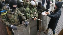 A volunteer distributes buns to anti-government protesters in central Kiev February 8, 2014. (GLEB GARANICH/REUTERS)