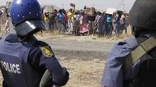 Armed policemen keep an eye on protesting women at the Lonmin mine near Rustenburg, South Africa, Friday Aug. 17, 2012. (Denis Farrell/AP)