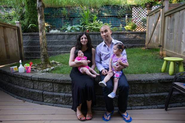 Rosine Hage-Moussa, left, and Darin Wong hold their two daughters, Madeline, 2, and Celine, two months, in the small backyard of their Port Moody, B.C., townhouse on Thursday.