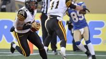 Hamilton Tiger-Cats' Arthur Hobbs (24) intercepts the ball in the end zone against the Winnipeg Blue Bombers during the second half of CFL action in Winnipeg Saturday, November 2, 2013. (Fred Greenslade/THE CANADIAN PRESS)