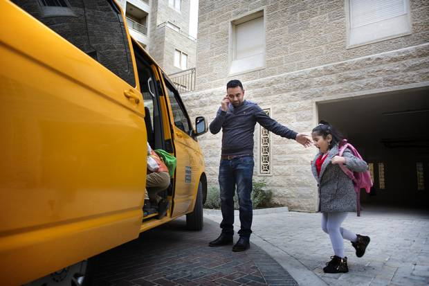 Fadi Salameh loads his son Yacoub, 4, and daughter Nour, 6, into the car for the trek for school.