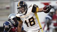 Hamilton Tiger-Cats receiver Mike Morreale tries to get away from Montreal Alouette Richard Karikari during a game in Montreal on June 22, 2005. (RYAN REMIORZ)