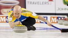 Team Alberta's skip Kevin Koe throws a rock in the first end against team British Columbia during the championship draw at the 2014 Tim Hortons Brier curling championships in Kamloops, British Columbia March 9, 2014. (BEN NELMS/REUTERS)