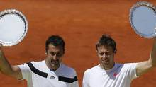Daniel Nestor from Canada, right and Nenad Zimonjic from Serbia , left, hold their trophies after a Madrid Open tennis tournament doubles final match against Bob Bryan and Mike Bryan from the U.S, in Madrid, Spain, Sunday, May 11, 2014. (AP)