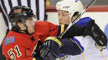 Calgary Flames' Roman Horak (L) tries to get past St. Louis Blues' Kent Huskins during the first period of their NHL hockey game in Calgary, Alberta, October 28, 2011. REUTERS/Todd Korol (TODD KOROL)
