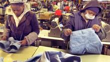 Workers at a garment factory in Maseru, capital of Lesotho. The factory is owned by CGM, a Taiwanese-based group. Workers wear jackets and hats because of the cold winter weather. They are also required to wear face masks to protect their lungs from dust and fibres, but many workers do not. (Geoffrey York/Globe and Mail)