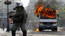 Riot policemen defend their position beside a burning van during violent protests against austerity measures in Athens' Syntagma (Constitution) square, June 28, 2011. (Yannis Behrakis/Reuters/Yannis Behrakis/Reuters)