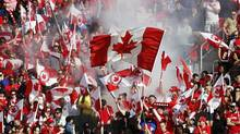 Spectators wave flags as Canada and the U.S. play during the second half of their friendly women's soccer match in Toronto, June 2, 2013. (MARK BLINCH/REUTERS)
