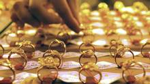 A sales assistant arranges the gold rings at a store in Shenyang in northeast China's Liaoning province. (Associated Press)