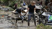 Residents shovel layers of mud flood debris in Calgary (ANDY CLARK/REUTERS)