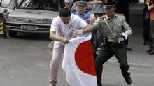 Chinese security personnel try to stop a Chinese man as he prepares to burn Japanese national flag outside the Japanese embassy in Beijing Tuesday, Sept. 11, 2012. Chinese government ships are patrolling near contested East China Sea islands in a show of anger after Tokyo moved to assert its control in the area. (Ng Han Guan/AP)