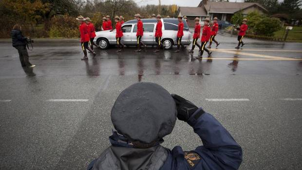 RCMP officers walk next to the hearse carrying the casket of RCMP Const. Adrian Oliver during his funeral in Langley, British Columbia. Const. Oliver was killed in a crash earlier this week in Surrey. (BEN NELMS/REUTERS)