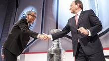 Rogers CEO Nadir Mohamed (left) shakes hands with NHL Commissioner Gary Betman following a news conference in Toront