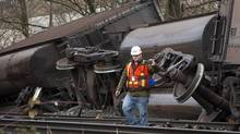 Inspectors look over 3 CP train cars that flipped after derailing in the Vancouver suburb of Burnaby, B.C. on Jan. 11, 2014. (Ben Nelms For The Globe and Mail)