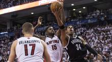 Brooklyn Nets' Paul Pierce (right) is fouled by Toronto Raptors' Amir Johnson (middle) as Raptors' Jonas Valanciunas looks on in Toronto, Saturday, April 19, 2014. (Chris Young/THE CANADIAN PRESS)