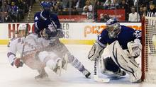New York Rangers' Carl Hagelin loses his footing driving to the net past Toronto Maple Leafs' Cody Franson and in front of goalie James Reimer, during the third period of their NHL hockey game in Toronto April 8, 2013. (FRED THORNHILL/REUTERS)
