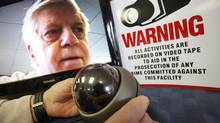 Russell Patterson (face in monitor) adjusts a surveillance camera in his Winnipeg store on Jan. 25, 2012. (John Woods for The Globe and Mail)