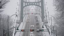 Snow covers the Lions Gate bridge in Vancouver, B.C. Friday, Dec. 20, 2013. A wet heavy snowstorm has blanketed the lower mainland with snow making driving dangerous. (JONATHAN HAYWARD/THE CANADIAN PRESS)