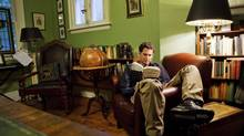 Kenneth Oppel reads in the library of his Toronto home. (Della Rollins/The Globe and Mail)