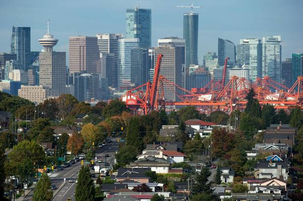 The downtown skyline and cranes at Port Metro Vancouver are seen in the distance behind houses in east Vancouver, B.C., on Sept. 23, 2015. Vancouver is becoming a city where many of its residents are shuffling in together and squeezing in at a steady pace.