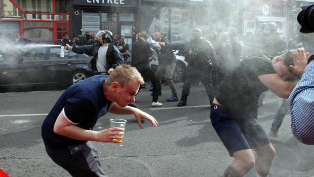 English fans run after getting sprayed with pepper spray by French police during scuffles in downtown Lille, northern France, June 15, 2016, one day ahead of the Euro 2016 Group B soccer match against Wales in nearby Lens.