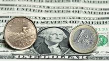 A Canadian dollar, left, and a Euro are seen next to a series of U.S. dollars. Legendary U.S. economist Milton Friedman was the most well-known of the rules-based crowd, famously calling for the Fed to be replaced by a computer that would simply let the money supply grow at a steady rate. (Paul Chiasson/THE CANADIAN PRESS)